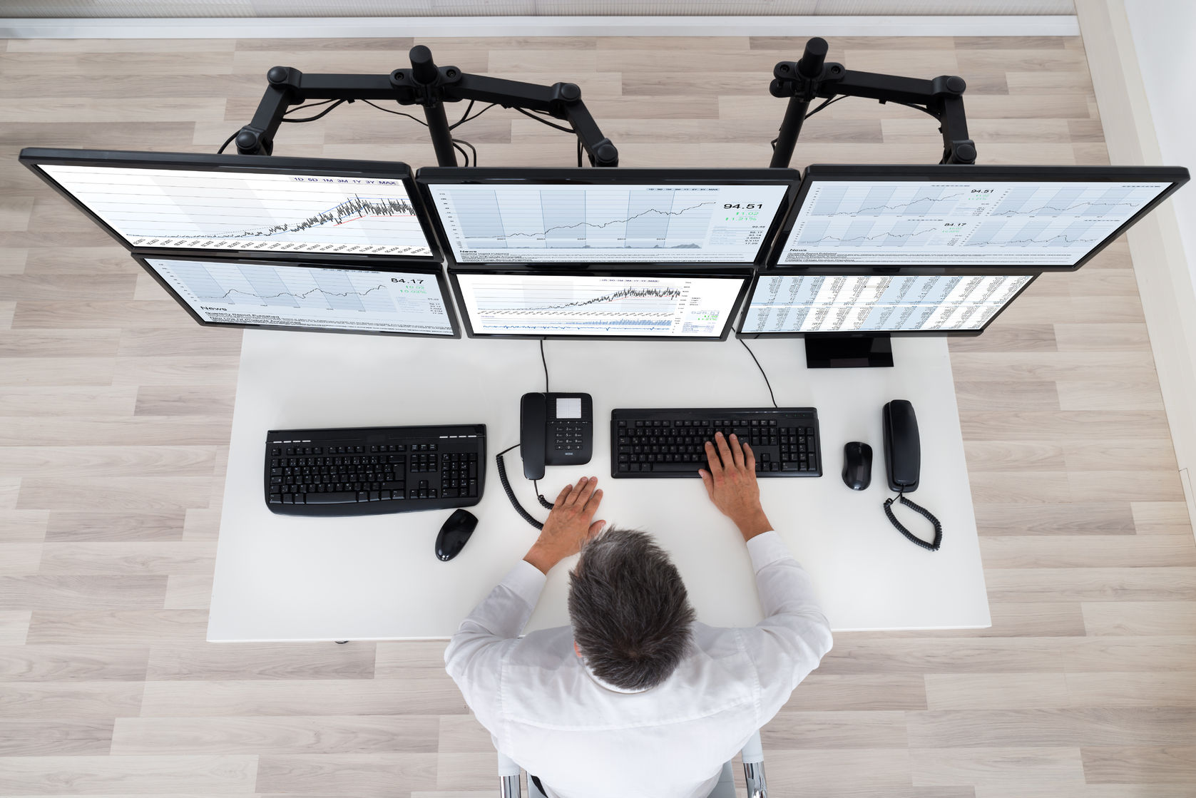 rear view of stock market broker looking at graphs at desk in office