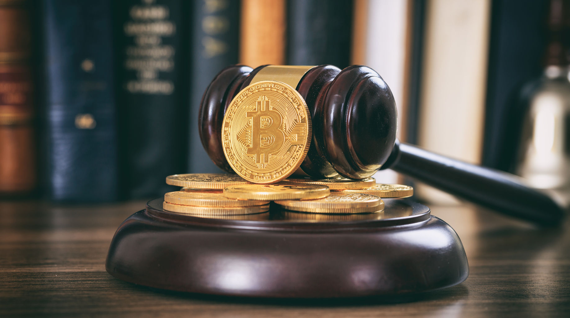 law or auction gavel and bitcoins on a wooden desk, dark background - cryptocurrencies legal